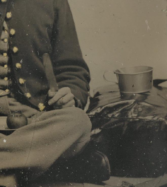 "Unidentified Soldier posed in a Photographer's Tent or Studio. He has a 3-tine fork in one hand, and butter knife in the other, with an apple on his plate. But notice his shorter than ""standard"" tin cup, resting on top of his knapsack."